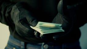 Homem nas luvas pretas que guardam a pilha de dinheiro, conceito do crime filme