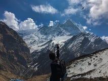 Homem nas montanhas que acenam ao helicóptero que passa perto Nepal, circuito de Annapurna imagem de stock royalty free