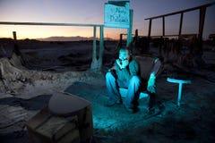 Homem nas ruínas que presta atenção à televisão imagens de stock
