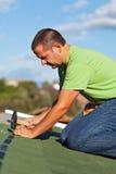 Homem nas telhas do telhado do betume da asseguração do telhado foto de stock