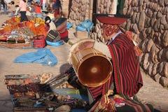 Homem nativo do Inca que vende lembranças e que joga cilindros, mercado de Chinchero, Cusco, Peru fotos de stock royalty free