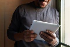 Homem negro afro-americano que usa a tabuleta eletrônica em casa imagem de stock