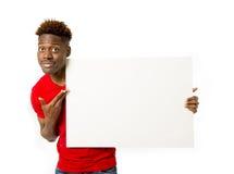 Homem negro americano que guarda e que mostra o quadro de avisos do painel vazio com espaço da cópia Fotografia de Stock