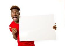 Homem negro americano que guarda e que mostra o quadro de avisos do painel vazio com espaço da cópia Fotografia de Stock Royalty Free