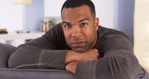 Homem negro de sorriso que descansa no sofá fotos de stock royalty free