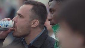 Homem negro do bandido na máscara protetora verde que fala ao indivíduo no evento aglomerado filme