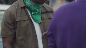 Homem negro do gângster que usa o telefone esperto que texting no evento aglomerado filme
