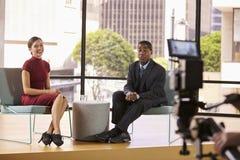Homem negro e mulher branca em olhar ajustado da entrevista da tevê à câmera imagens de stock