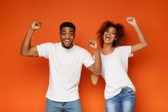 Homem negro feliz e mulher emocionais que apreciam o sucesso junto fotos de stock royalty free