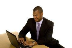 Homem negro no terno que trabalha no portátil Imagem de Stock