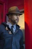 Homem negro novo com Fedora na entrada vermelha Fotografia de Stock Royalty Free
