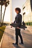 Homem negro novo com skate que anda na rua e na vista fotografia de stock royalty free