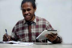Homem negro novo de sorriso que trabalha e que estuda mantendo o portátil e a pena que fazem trabalhos de casa imagens de stock royalty free