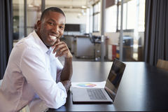 Homem negro novo no escritório com portátil que sorri à câmera Foto de Stock Royalty Free