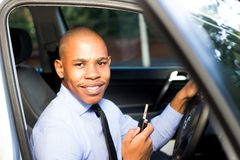 Homem negro novo que sorri ao sentar-se em seu carro Foto de Stock Royalty Free