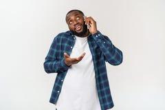Homem negro novo que sorri e que fala no telefone celular imagem de stock