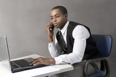 Homem negro novo que trabalha em seu portátil Foto de Stock