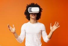 Homem negro novo que veste auriculares da realidade virtual imagem de stock royalty free