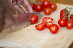 Homem negro que corta tomates Imagem de Stock