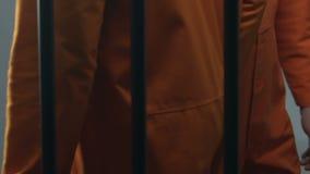 Homem negro que dá a dinheiro o prisioneiro caucasiano, pagamento para o favor ilegal na cadeia vídeos de arquivo
