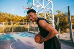 Homem negro que joga o basquetebol, bola da rua, homem que joga, competições de esporte, afro, retrato exterior, jogos do esporte Imagem de Stock