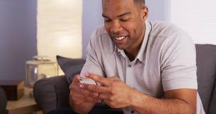 Homem negro que sorri e que texting no smartphone fotos de stock royalty free