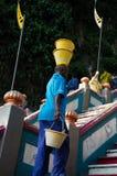 Homem negro superior com as cubetas em suas cabeça e mão acima das escadas fotografia de stock