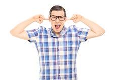 Homem nervoso que obstrui suas orelhas Imagem de Stock