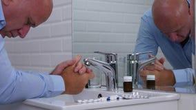 Homem nervoso que sofre uma dor no banheiro que olha aos comprimidos e às drogas médicos video estoque
