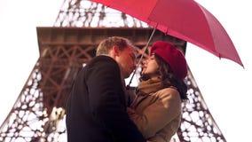 Homem no amor aproximadamente para beijar a mulher bonita sob o guarda-chuva, data romântica em Paris fotografia de stock