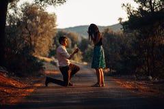 Homem no amor que propõe uma mulher surpreendida, chocada casá-lo no por do sol Conceito da proposta, do acoplamento e do casamen imagem de stock