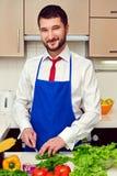 Homem no avental azul que prepara-se na cozinha Fotos de Stock