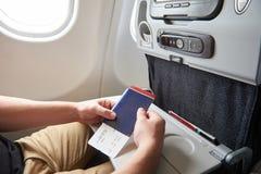 Homem no avião com passaporte à disposição Imagem de Stock