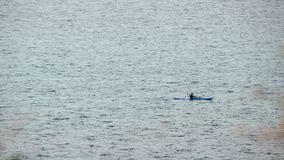 Homem no barco de fileira no mar aberto imagens de stock