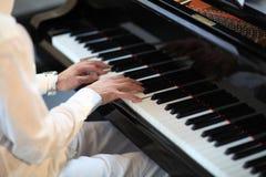Homem no branco que joga o piano grande Imagem de Stock Royalty Free
