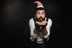 Homem no brilho de prata de sopro do chapéu de Santa Claus sobre o fundo preto Fotografia de Stock