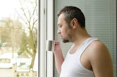 Homem no café bebendo e em olhar da manhã para fora a janela Fotografia de Stock