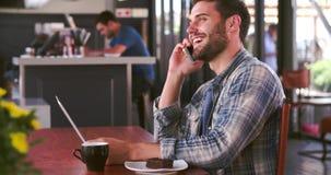 Homem no café que trabalha no portátil e no telefone de resposta video estoque