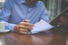 Homem no café usando a tabuleta digital e escrevendo no papel C fotografia de stock royalty free