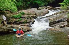 Homem no caiaque em uma cachoeira fotografia de stock royalty free