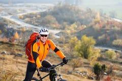 Homem no capacete e nos vidros, com estada da trouxa na bicicleta sob a paisagem com rochas e monte fotos de stock