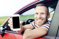 Homem no carro que mostra o telefone esperto foto de stock royalty free