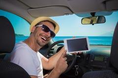 Homem no carro que mostra a tela vazia o dispositivo digital da tabuleta Viaje imagens de stock royalty free