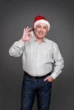 Homem no chapéu de Papai Noel que mostra o sinal aprovado Fotos de Stock