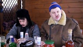 Homem no chap?u e no revestimento azuis com seu chap?u vestindo do amigo com aletas da orelha para comer e falar vídeos de arquivo