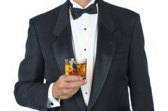 Homem no cocktail da terra arrendada do smoking foto de stock