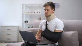 Homem no colar da espuma e no estilingue cervicais do braço que datilografa uma mão no portátil, autônomo video estoque