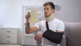 Homem no colar da espuma e no estilingue cervicais do braço que lê a conta médica, preço chocante vídeos de arquivo
