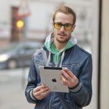 Homem no computador da tabuleta de Ipad do uso da rua Fotografia de Stock Royalty Free