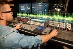 Homem no console de mistura no estúdio de gravação da música imagem de stock